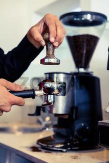 Barista pressing down fresh coffee grounds