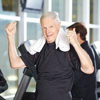 Alter Mann auf Laufband im Fitnesscenter