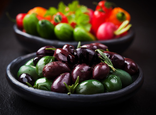 Variation of olives with raw snack vegetable in the background