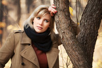 Sad beautiful woman in autumn forest