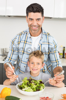 Smiling father tossing salad with his cute son