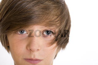 Closeup of a cute teenage boy smiling into the camera, isolated on white