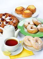 still life of setout table with baking pies, donuts, tee cup and pot.
