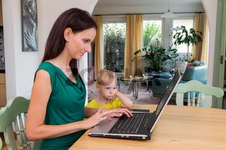 Frau mit Laptop und Kind