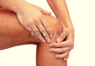 close up of female hands holding knee