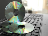 Software CD on laptop keyboard. Compact disks.