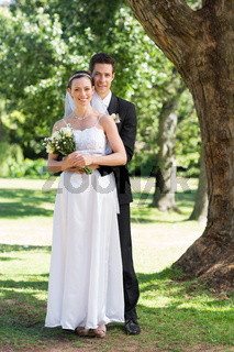 Groom and bride with flower bouquet in park