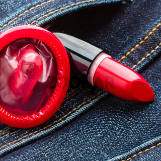 Closeup red condom on jeans pocket.