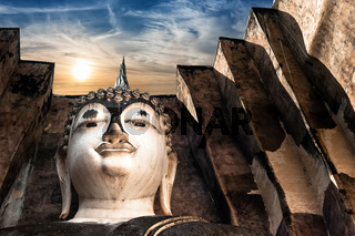 Ancient architecture of Buddhist temples in Sukhothai Historical Park. Statue of  Buddha Phra Achana at Wat Si Chum Temple under sunset sky. Thailand