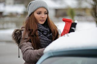 Junge Frau fegt Schnee von ihrem Auto