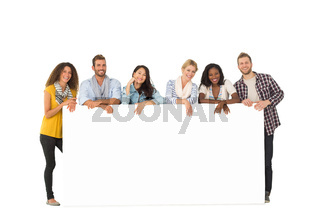 Smiling group of young friends leaning on large poster
