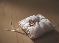 Golden rings on a white pillow