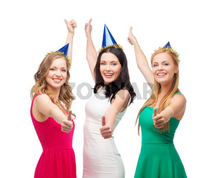 three women wearing hats and showing thumbs up