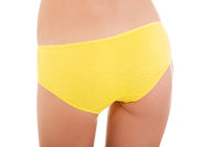 Slim tanned woman's body in yellow panties.