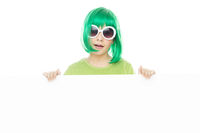 Cute young girl in a green wig holding a sign