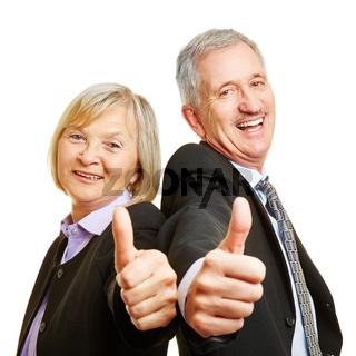 Senioren als Geschäftsleute halten Daumen hoch