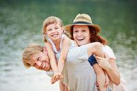 Lachende Familie am Wasser im Sommer
