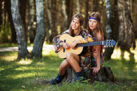 Two hippie girls with guitar in a summer forest