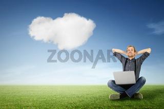 Mann mit Laptop entspannt auf grüner Wiese