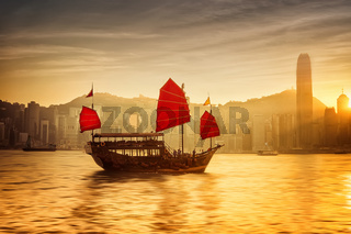 Sunset at Hong Kong with traditional cruise sailboat