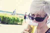 One Senior Woman drinking a glass of beer