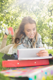 Pretty young student lying on the grass studying with her tablet pc