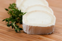 Goat cheese with thyme on a wooden board.