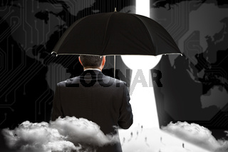 Composite image of mature businessman holding an umbrella
