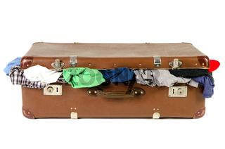 alter Koffer voll mit Kleidung vor weißem Hintergrund