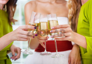 Hands of the bride and bridal friends holding glass with champagne