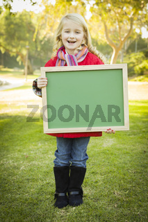 Cute Girl Holding a Green Chalkboard Wearing Winter Coat Outdoors