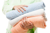 Woman hand holding spa towels stack white isolated