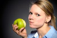 junge blonde Frau mit einem grünen Apfel