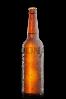 Beer bottle with water drops and frost isolated on black