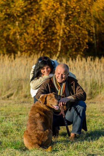 Cheerful couple with dog in autumn countryside