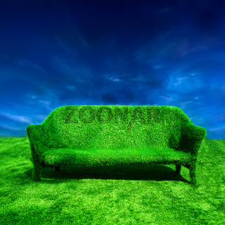 Ecology concept background. Grassy sofa standing at green grass over blue sky