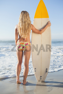Gorgeous blonde surfer in bikini holding her board