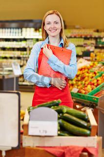 Junge Verkäuferin im Biomarkt mit Klemmbrett