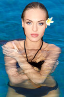 Exotic young woman with frangipani in her hair