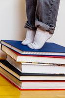 Kind steht auf einem Stapel Bücher