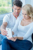 Couple reading a text message with consternation