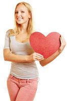 Frau hält ein großes rotes Herz