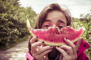 girl is holding a bitten slice of melon in front of here face, vintage color filter