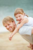 Vater trägt Tochter huckepack im Sommer