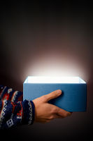 blue gift box with light in front of black background