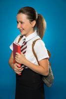 Happy young schoolgirl carrying a tex book