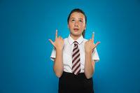 Attractive schoolgirl pointing above her head