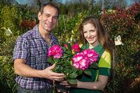 Female florist hands flower to customer in shop
