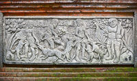 Images of people and dogs carved on a stone plate. Indonesia, Bali