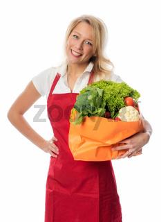 frau mit schürze trägt tasche mit gemüse